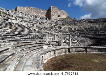 View of Miletus amphitheater in Aydin, Turkey with stone stairs on bright blue sky background.
