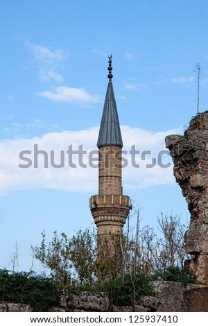View of minaret of Tekeli Mehmet Pasa Mosque rising above ruins in Antalya Turkey - stock photo
