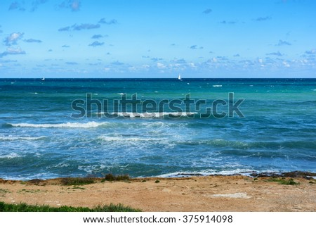 View of moderate Mediterranean sea, waves with sea foam, rocky coast and white sailing ships near the horizon, Spain, Europe
