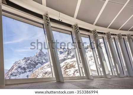 View of Mont Blanc and Aiguille Noire de Peuterey peak covered of snow, trough windows of a modern building.