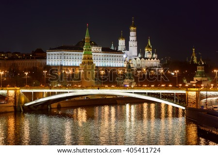 View of Moscow red brick Kremlin with cathedral tower, highlighted bridge over Moskva river at night and colored street lights reflection on it. Russia - stock photo
