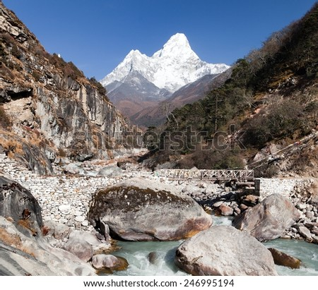 VIew of mount Ama Dablam with stony and wooden bridge above river - way to everest base camp - Khumbu valley - Nepal - stock photo