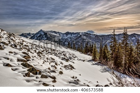 View of Mount Rainier from atop Mailbox Peak and Snow Covered Rock and Boulder Field  - stock photo