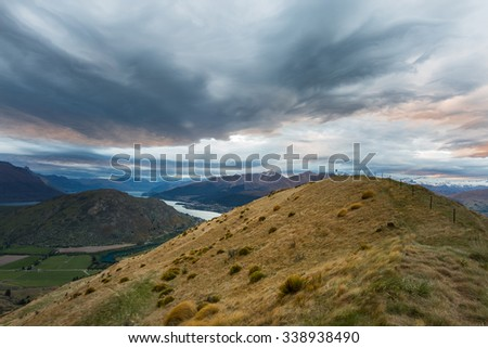 view of mountain, lake and dramatic clouds at sunset in Queenstown, New Zealand - stock photo