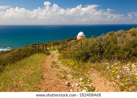 View of mountain road with trees, cloudy sky, Mediterranean sea and Christian Chapel on the background - stock photo