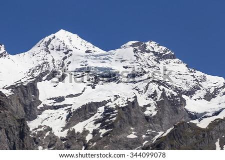 View of mountain rocks and ice-capped Swiss Alps near Oeschinensee (Oeschinen lake), on Bernese Oberland, Switzerland - stock photo