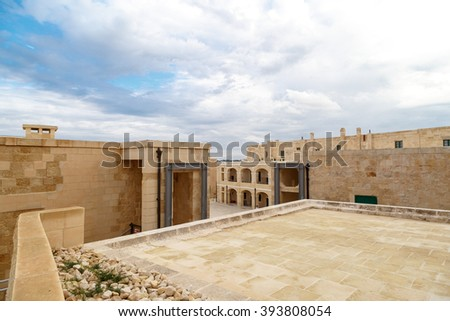 View of National War Museum in Valletta, Malta with high yellow stone walls, on cloudy sky background.