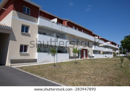 View of  newly built modern block of flats under blue sky - stock photo