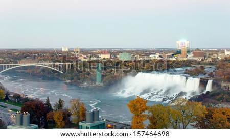View of Niagara Falls, New York from Niagara Falls, Canada of the American Falls, Rainbow Bridge and the Niagara River as dusk settles in on a late autumn evening in wide screen, 16.x9 resolution.