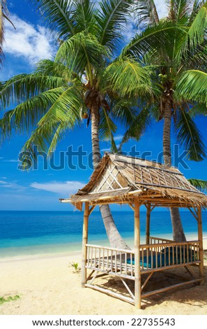 View of nice empty sandy beach with some tropical hut. - stock photo