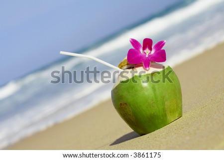 view of nice fresh tropic cocktail decorated with orchid on sandy beach - stock photo
