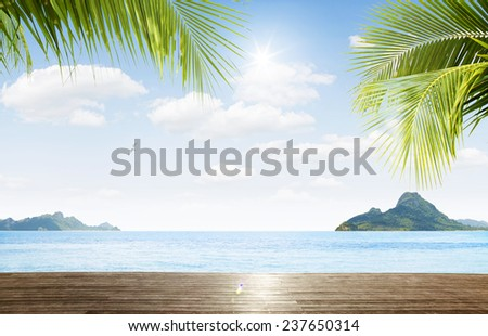 view of nice  palms,blue ocean  with tropical islands in the distance - stock photo