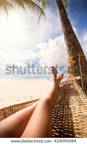 view of nice sexy smooth woman's legs in a hammock on tropical resort - stock photo
