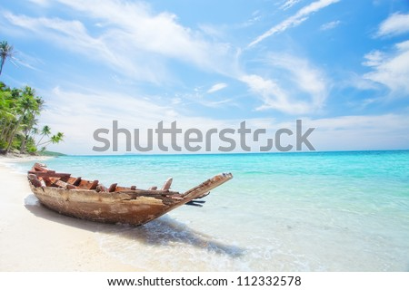 View of nice tropical  beach  with old boat - stock photo