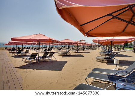 View of nice tropical empty sandy beach with umbrella and beach chair - stock photo