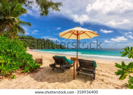View of nice tropical empty sandy beach with umbrella and beach chair, Seychelles - stock photo