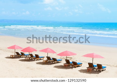 View of nice tropical empty sandy beach with umbrellas and beach beds - stock photo