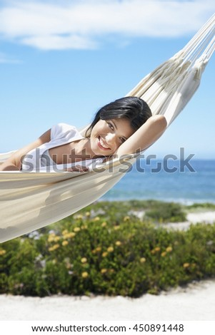 view of nice woman lounging in hammock in tropical environment in summer vacation day