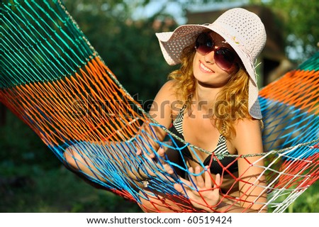 View of nice woman wearing oversized shades and lounging in hammock - stock photo