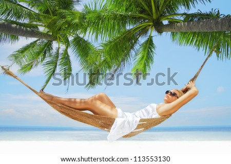 view of nice young lady swinging  in hummock on tropical beach - stock photo
