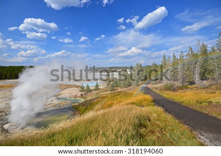 view of Norris Geyser Basin and rainbow in Yellowstone National Park, Wyoming, USA - stock photo