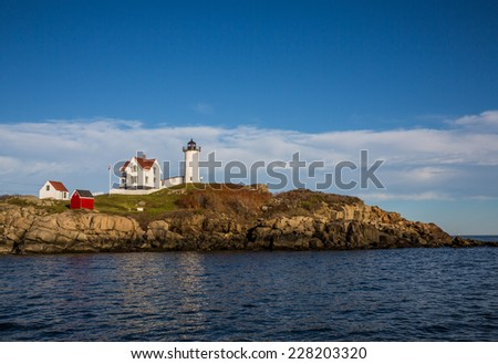 View of Nubble lighthouse in Maine in New England USA showing rocky coastline against blue sky. - stock photo