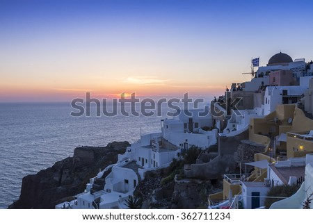 View of Oia traditional white houses of Oia at sunset in Santorini, Greece.