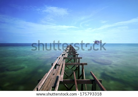view of old broken jetty during sunny day with coral and green sea water in long exposure. noise may visible due to long exposure and high iso - stock photo