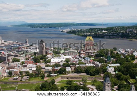 View of old city of Quebec with the St. Lawrence river and Orleans in background and city wall in foreground.  Chateau Frontenac landmark can be seen - stock photo
