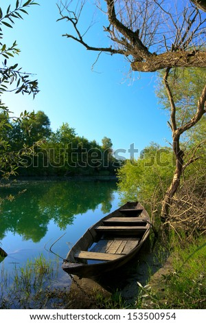 View of old holey boat on the river in national park Skadar Lake, Montenegro - stock photo