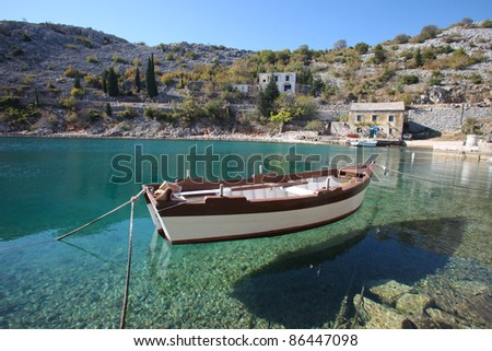 View of old stone house with a wooden boat moored in little bay - stock photo