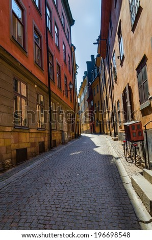 View of one of the streets in Stockholm, with beautiful colored houses and cobbled street - stock photo
