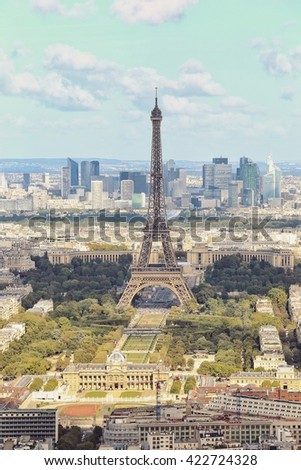 View of Paris city roofs with Eiffel Tower from above and blue sky in vintage style, France - stock photo