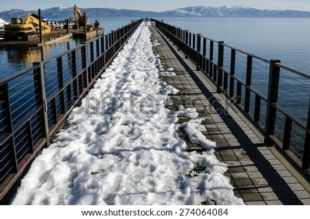 View of partly covered pier with snow, Lake Tahoe - stock photo