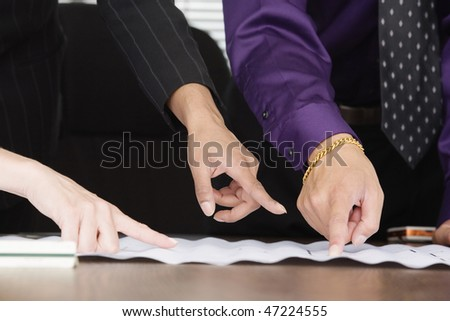 View of people pointing fingers on paper.