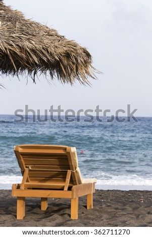 view of Perissa beach on the Greek island of Santorini with sunbeds and umbrellas. Beach is covered with fine black sand, and drops off sharply into the water.