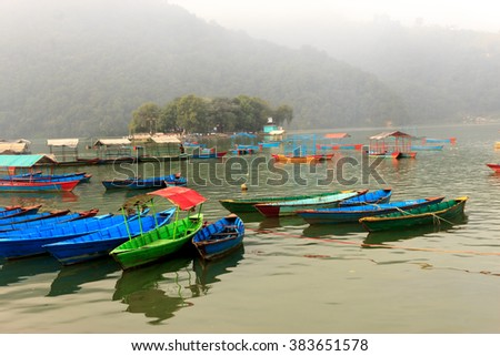 View of Phewa lake with colourful boats on the water in Pokhara,Nepal. - stock photo