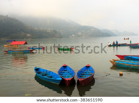 View of Phewa lake with colourful boats together in Pokhara,Nepal. - stock photo