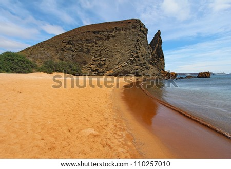 View of Pinnacle Rock and breaking waves from the red sand beach on Bartolome Island, Galapagos National Park, Ecuador, with Sullivan Bay, cruise ships, and Santiago Island in the background - stock photo
