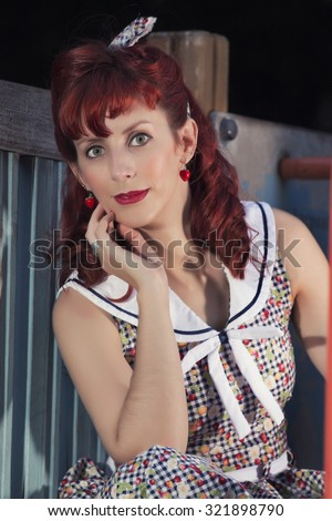 View of pinup young woman in vintage style clothing on a playground.