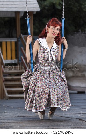 View of pinup young woman in vintage style clothing on a playground. - stock photo