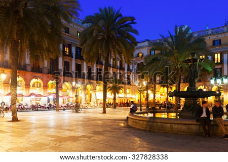 View of Placa Reial with fountain and restaurants in evening. Barcelona, Catalonia