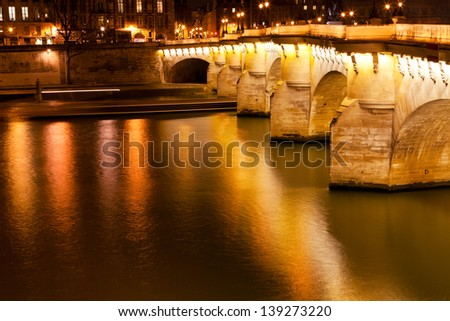 view of Pont Neuf through Seine river in Paris at night