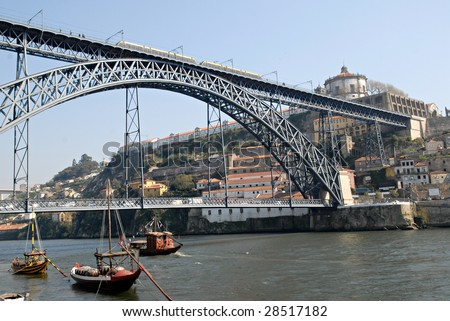 View of Porto city, Portugal. Porto city, excursion boat in the river Douro and the Bridge of Luis I with tram, Portugal.  It was made by design o? Gustaf Eiffel. Point of interest in Portugal.