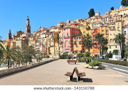 View of promenade and old medieval town with multicolored houses of Menton on french riviera in France. - stock photo