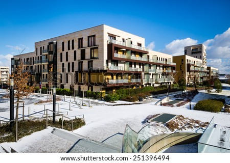 View of public park with newly built modern block of flats in winter - stock photo