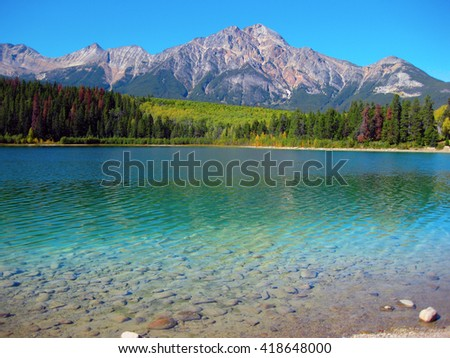 View of Pyramid Mountain Jasper across a glacier lake - stock photo