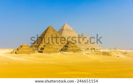 View of pyramids from the Giza Plateau: three Queens' Pyramids, the Pyramid of Menkaure, the Pyramid of Khafre and the Great Pyramid of Giza (Khufu or Cheops) - stock photo