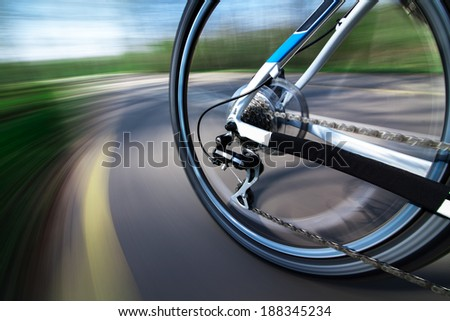 View of rear bicycle wheel with chain and cassette in motion - stock photo