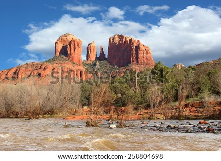 View of red  mountain range. Blue skies and white puffy clouds fill the sky as a cool breeze blows shaking the trees leaves. Wild raging river filled with fish and rocks sweep through the foreground.  - stock photo